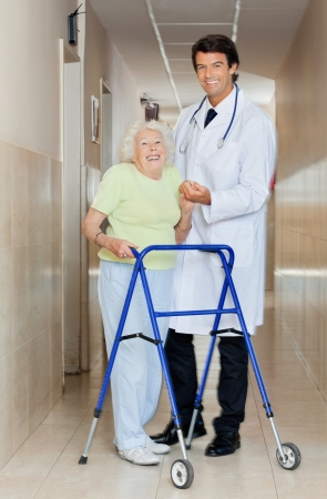 Full length portrait of a young male doctor assisting senior woman with her walker Stock Photo - 14350952
