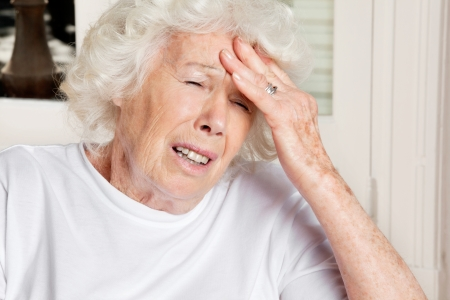 Senior woman with eyes closed suffering from headache photo