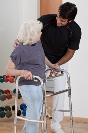 A therapist assisting a senior woman onto her walker  photo
