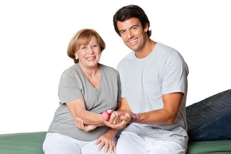 muskeltraining: Portrait eines gl�cklichen jungen Therapeuten geben Muskeltraining f�r Ellenbogengelenk �ber wei�em Hintergrund Lizenzfreie Bilder