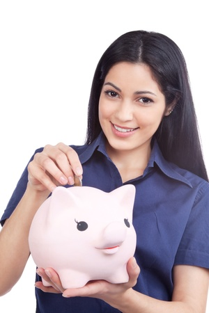 woman holding money: Smiling woman holding piggy bank and coin isolated on white background