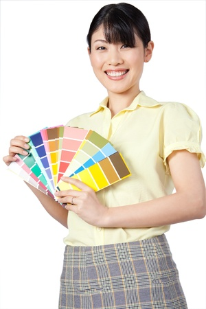 Happy young Asian woman showing color chart isolated on white background  photo
