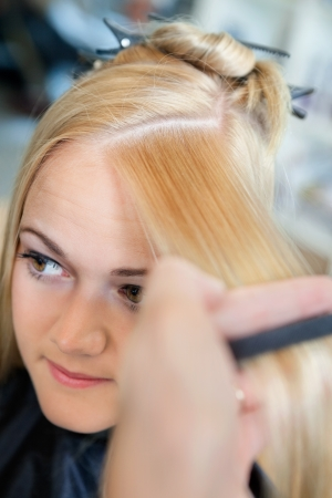 horizontal haircut: Close up of young female getting a hairdo from hairstylist at salon Stock Photo
