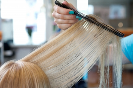 horizontal haircut: Cropped image of hairdresser s hand combing hair of female customer at salon
