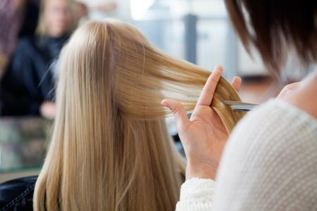 Primo piano di parrucchiere dare un nuovo taglio di capelli al cliente femminile salone Archivio Fotografico