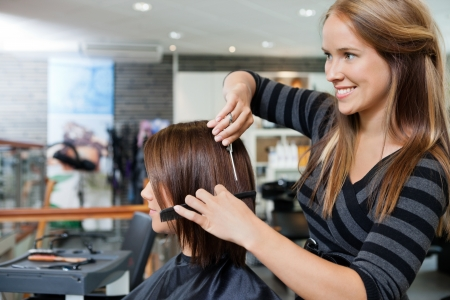 Stylist: Peluquería joven hermosa que da un nuevo corte de pelo a la clienta en el salón de Foto de archivo