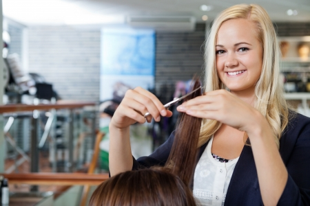 Portrait of happy young female beautician giving a haircut to female at parlor photo