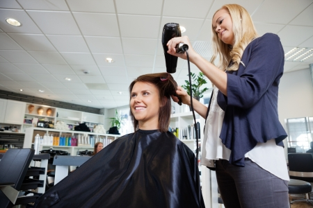Young beautician blow drying hair of customer after a haircut photo