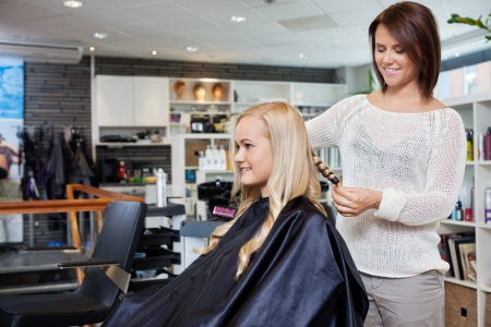 stylist: Young woman having her hair styled by beautician at parlor Stock Photo