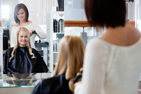 Mirror reflection of young woman getting her curled by stylist at parlor photo