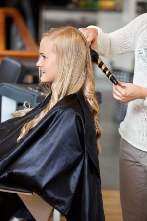 peluqueria: Vista lateral de una mujer joven que consigue el pelo rizado por la esteticista en el sal�n de