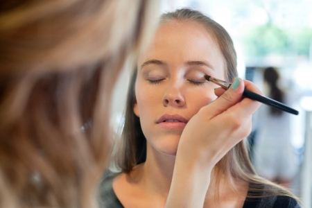 close up of beautician applying eye shadow to woman at parlor photo