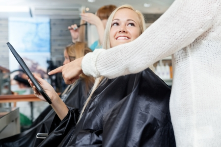 Woman looking at hairdresser while she points on digital tablet s screen photo