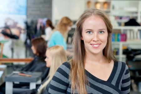 Portrait of young female hairdresser smiling with people in background photo