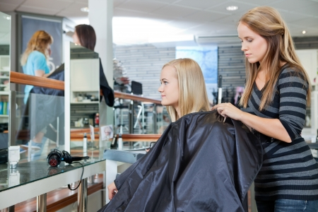 hairdresser's parlor: Young hairdresser making preparation before giving a haircut to female customer at parlor