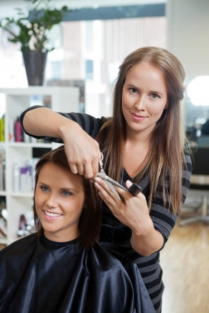 Portrait of pretty female beautician cutting hair of customer at parlor photo