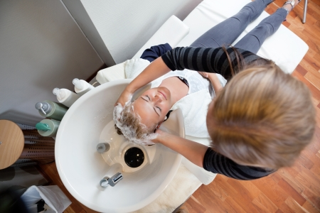 High angle view of female beautician washing customer s hair with shampoo at beauty salon photo