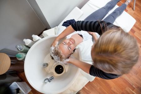 champu: Vista de �ngulo alto de pelo clienta lavado con champ� esteticista s en el sal�n de belleza