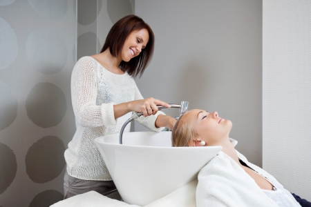 beauty parlour: Beautician smiling while washing hair of female customer at beauty salon