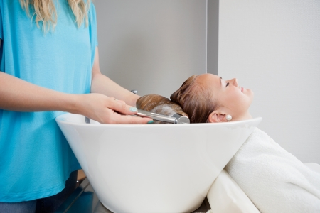 Relaxed young woman getting her washed before haircut at beauty salon photo