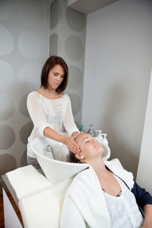 Young woman getting a massage while having hair wash at salon by hairdresser Stock Photo - 14454711