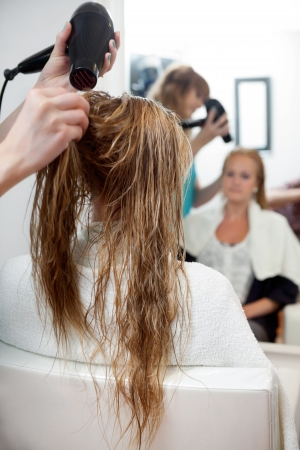 blow dryer: Hairdressers hands drying long blond hair with blow dryer at parlor