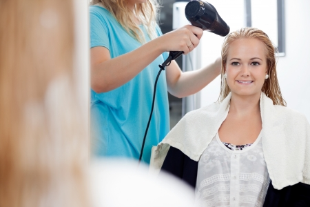 Mirror reflection of hairdresser drying long blond hair with blow dryer at parlor photo