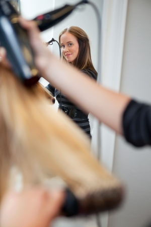 sylist: Mirror reflection of a beautiful professional hair stylist holding blow dryer Stock Photo