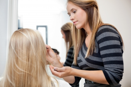 sylist: Pretty female artist applying make up to woman in parlor Stock Photo