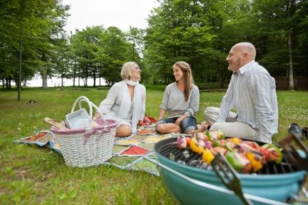 actividades recreativas: Cauc�sico grupo de amigos en el parque con un picnic barbacoa