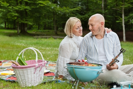 Mature couple in casual clothes looking at each other while on an outdoor picnic in forest park Stock Photo - 14454740