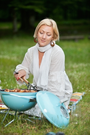 leisureliness: Beautiful mature woman in casual wear cooking food on a portable barbecue on a weekend outing