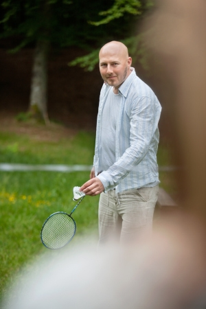 leisureliness: Portrait of mature man in casual wear with racquet and birdie ready to serve