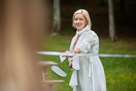 Portrait of a beautiful mature woman with racquet and shuttlecock ready to serve Stock Photo - 14454717