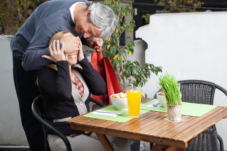 Middle aged man covering woman s eyes on breakfast table for surprise gift photo
