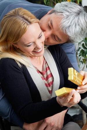 Affectionate middle aged man kissing woman as she opens present Stock Photo - 14508053