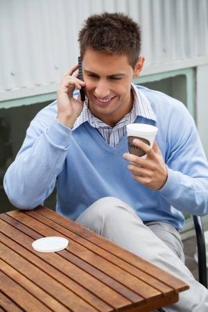 Handsome young man with disposable coffee cup communicating on cell phone while sitting at cafe photo