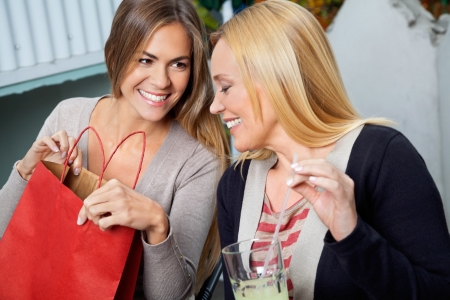 an old friend: Happy young woman showing purchases to mother while sitting together Stock Photo