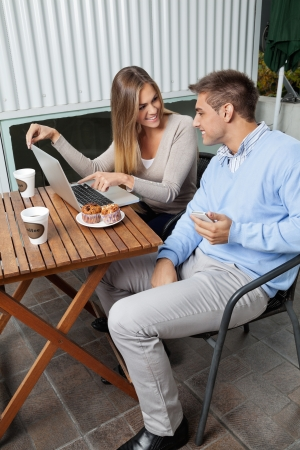 Young woman pointing at laptop screen to man while sitting at cafe photo