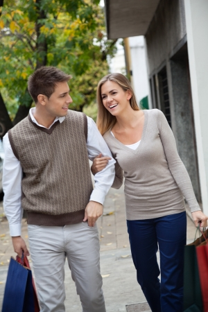 carrying girlfriend: Happy young couple walking together on pavement with shopping bags