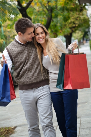 sidewalk talk: Happy young couple walking leisurely together on sidewalk with shopping bags Stock Photo