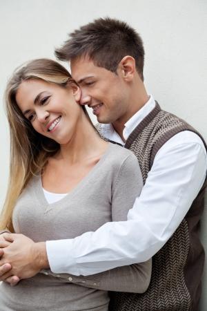 Hombre joven abrazando a una mujer hermosa por detr�s sobre el fondo de color Foto de archivo - 14508179