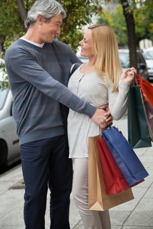 Happy middle aged man embracing woman on sidewalk while carrying shopping bags Stock Photo - 14508107