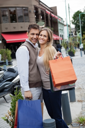 holiday spending: Portrait of cheerful young couple with shopping bags standing on sidewalk