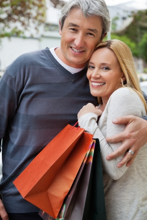 Portrait of a middle aged man embracing woman as she holds shopping bags photo