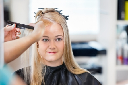Mirror reflection of young woman getting her hair combed before haircut at parlor Stock Photo - 14508091