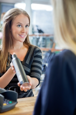 Young female hairstylist showing hair product to customer at counter photo
