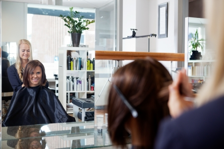 Mirror reflection of young woman getting a hairdo by beautician at parlor photo