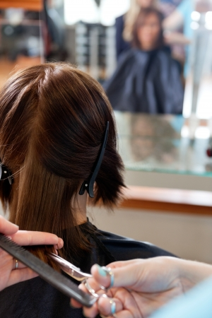 scissors hair: Close up of hairdresser giving a haircut to female customer at parlor