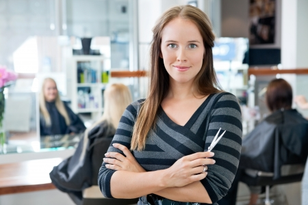 hairdressing scissors: Portrait of a confident female hairdresser standing hands folded with people in background Stock Photo